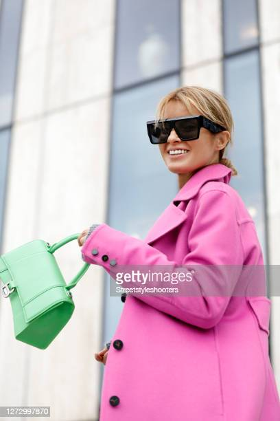 Influencer Gitta Banko wearing a long pink coat by Valentino a green bag by Balenciaga and sunglasses by Sonnenbrille Celine during a street style...