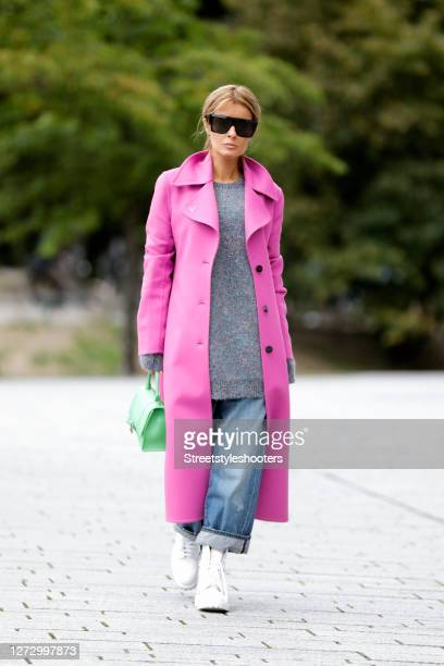 Influencer Gitta Banko wearing a long pink coat by Valentino a grey oversized pullover with multicolored sequin by Loewe light blue demin jeans by...