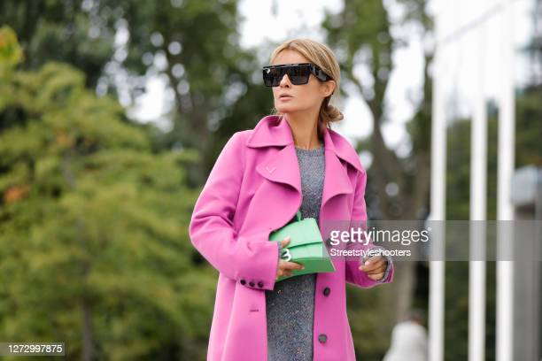 Influencer Gitta Banko wearing a long pink coat by Valentino a grey oversized pullover with multicolored sequin by Loewe a green bag by Balenciaga...