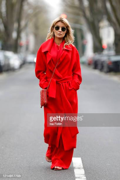 Influencer Gitta Banko wearing a long red coat and wide red pants by Boscana a red top by TRE by Natalie Ratabesi a red cell phone bag by Chanel red...