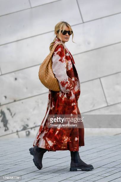 Influencer Gitta Banko wearing a long red-brown tie dye cashmere coat by Canessa, brown boots by Copenhagen Studios, sunglasses by Bottega Veneta and...