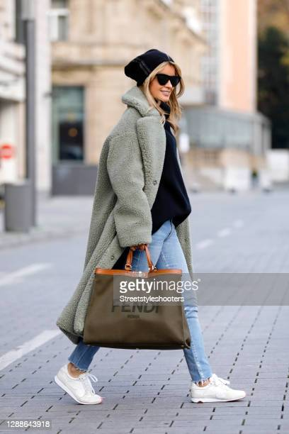 Influencer Gitta Banko wearing a long sage green colored teddy coat by Stand Studio, light blue ripped denim jeans by Balenciaga, a black cashmere...