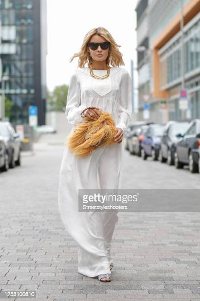 Influencer Gitta Banko wearing a long white maxi dress by Chanel, a gold necklace by Chanel, a brown bag with orange feathers by Marques Almeida,...