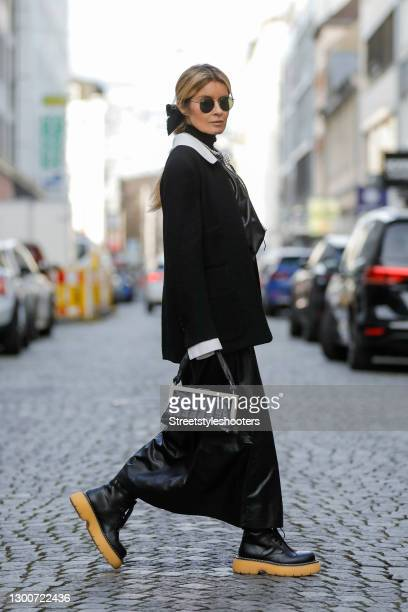 Influencer Gitta Banko wearing a low bubble ponytail hairstyle, a black bow hair clip by Chanel, a long black and white pearl necklace by Chanel, a...