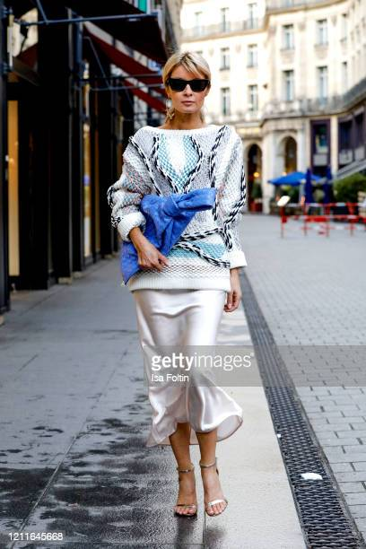 Influencer Gitta Banko, wearing a metallic-trimmed jaquard-knit sweater by Peter Pilotto, a white silk dress by Sly010, a indigo BV Twist bag by...