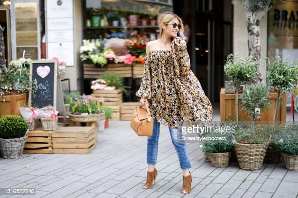 Influencer Gitta Banko wearing a multicolor off shoulder mini dress with floral print by Saint Laurent, blue denim jeans pants by Dsquared2, long...