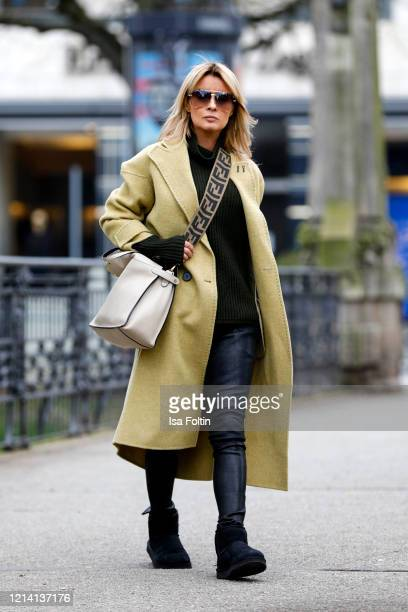 Influencer Gitta Banko wearing a mustard yellow coat by Tere Sha a dark green turtleneck sweater by Annette Goertz black leather pants by Hironae...