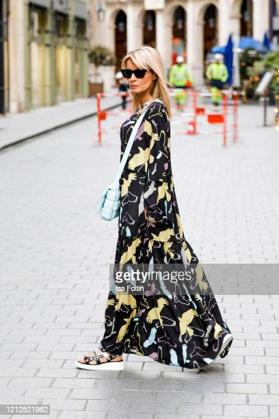 Influencer Gitta Banko, wearing a oversized black multicolor printed summer dress by Delicate Love, a topas colored padded cassette bag by Bottega...