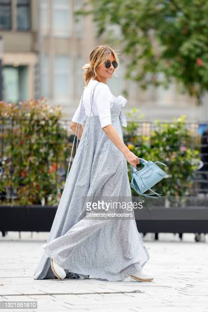 Influencer Gitta Banko wearing a pastel blue maxi dress with floral print and leg slit by Alanui, a white t-shirt by Closed, white clogs by Chanel, a...