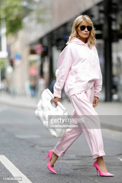 Influencer Gitta Banko, wearing a pastel pink hoodie and matching pastel pink sweatpants by Y-3, hot pink pumps by Balenciaga, a white leather bag...
