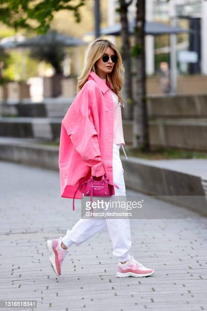 Influencer Gitta Banko wearing a pastel pink t-shirt by Palm Angels, a pink jacket by Valentino, white sweatpants by Alexander McQueen, a pink mini...