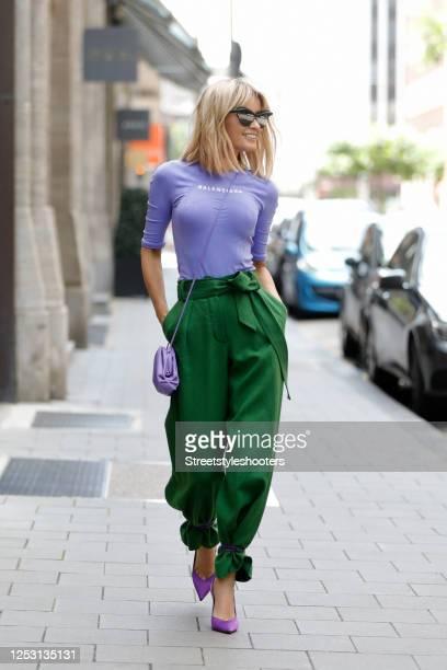 Influencer Gitta Banko wearing a purple mini pouch bag by Bottega Veneta, a purple athletic shirt by Balenciaga, sunglasses by Mykita x Maison...