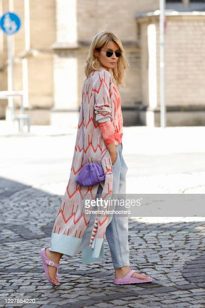 Influencer Gitta Banko, wearing a red and organge tie dye pullover by Zoe Ona, a long white cardigan with red and brown zig zag pattern by...