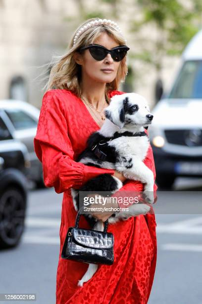 Influencer Gitta Banko wearing a red dress by The Andamane a black bag by Far a alice band with big white pearls by Mary Jane Clareroe and sunglasses...