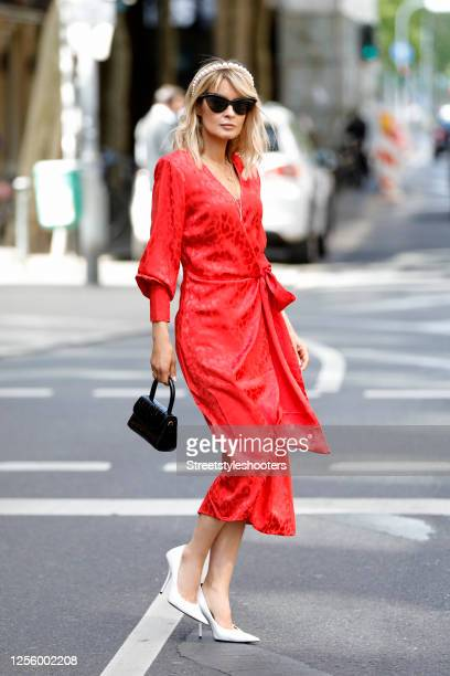 Influencer Gitta Banko, wearing a red dress by The Andamane, a black bag by Far, white pumps by Balenciaga, a alice band with big white pearls by...