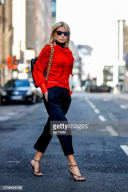 Influencer Gitta Banko, wearing a red silk blouse with a loop by Jacob Lee, dark blue pants by Nili Lotan, a black turtleneck pullover by Zara, black...