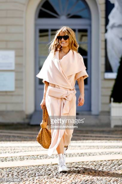 Influencer Gitta Banko wearing a rose colored oversize wrapper by Celeni whote boots by Common Project a cognac colored jodie bag by Bottega Veneta...