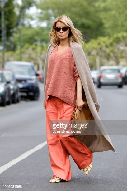 Influencer Gitta Banko, wearing a rust colored knitted pullover by Zoe Ona, hibiscus colored leather pants by Boscana, a sand colored long knitted...
