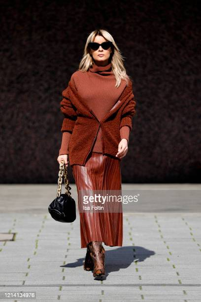 Influencer Gitta Banko wearing a rust colored turtleneck sweater a rust colored cardigan and a rust colored pleated leather shirt by Annette Goertz...