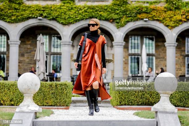 Influencer Gitta Banko, wearing a rust-colored velvet gown by Celini, a black turtleneck pullover by Boscana, a black 30 Montaigne bag by Dior, black...