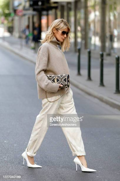 Influencer Gitta Banko wearing a sand colored knitted turtle neck pullover by Zoe Ona cream colored corduroy pants by Isabel Marant white pumps by...