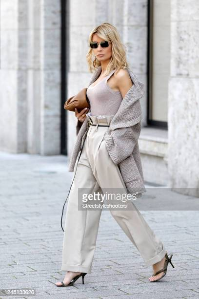Influencer Gitta Banko, wearing a sand colored tank top by H&M, beige high-waste paperbag pants by The Frankie Shop, an oversized sand colored...