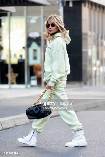 Influencer Gitta Banko wearing a seafoam green colored hoodie by Tekin Apparel, seafoam green colored jogger pants by Tekin Apparel, white combat...
