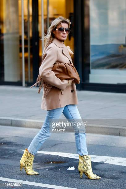 Influencer Gitta Banko wearing a short beige colored coat with fringe by The Kooples a blue Jeans by Closed yellow booties in python optic by Isabel...