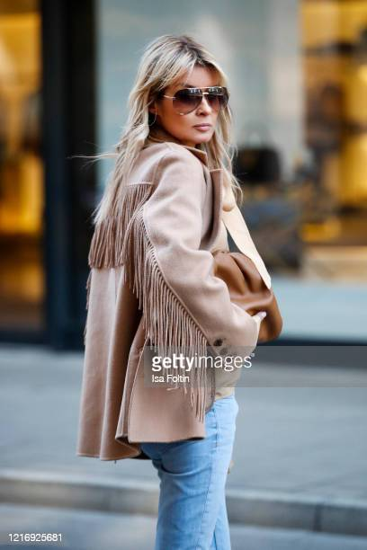 Influencer Gitta Banko wearing a short beige colored coat with fringe by The Kooples a blue Jeans by Closed a caramel colored pouch bag by Bottega...