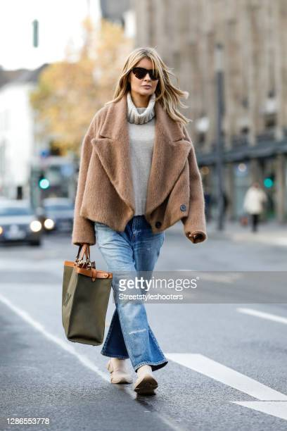 Influencer Gitta Banko wearing a short camel colored teddy jacket by Liviana Conti, light blue denim jeans by Saint Laurent, knitted beige 2.0 speed...
