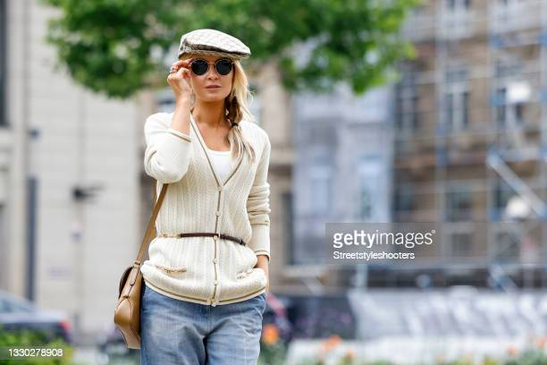 Influencer Gitta Banko wearing a side braid hairstyle, a cream colored knitted cardigan by Gucci, light blue flared denim jeans pants by Gucci, a...