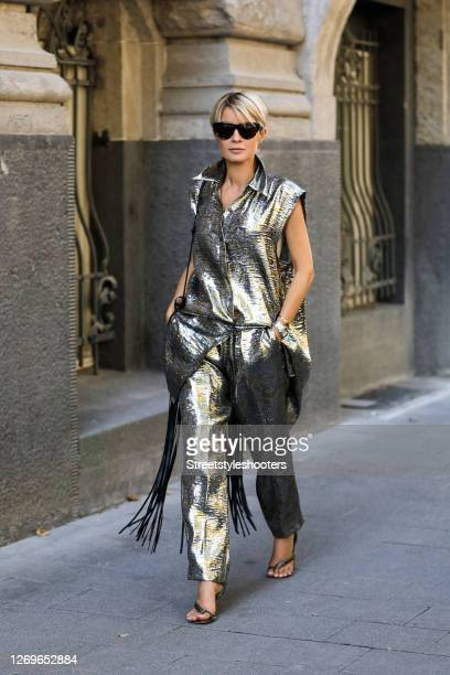 Influencer Gitta Banko wearing a silver and gold colored sleeveless blouse and matching pants by Dries van Noten, python wrap sandals by Bottega...