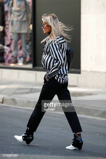 Influencer Gitta Banko wearing a striped blouse by Jacob Lee black pants by Tere Sha booties by Chanel a black chain pouch bag by Bottega Veneta and...