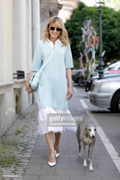Influencer Gitta Banko, wearing a white and light blue dress by Streffen Schraut, white pumps by Balenciaga, a light blue padded cassette bag by...