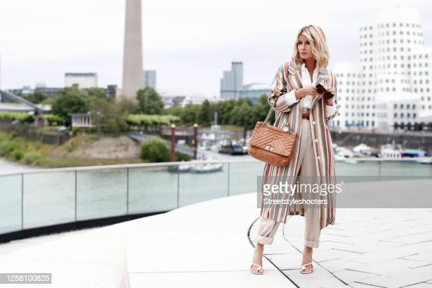 Influencer Gitta Banko wearing a white blouse with lace details by Zara, beige pants by Zara, a long striped multicolored coat by Gitta Banko, a...