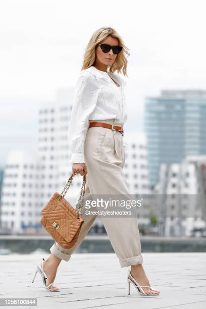 Influencer Gitta Banko wearing a white blouse with lace details by Zara, beige pants by Zara, a cognac colored leather bag by Chanel, cream colored...