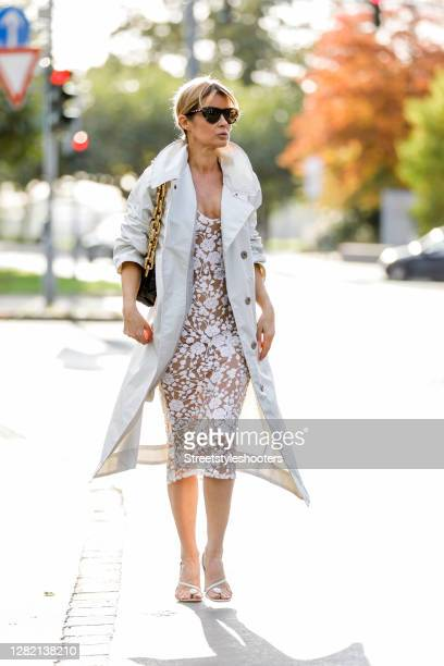 Influencer Gitta Banko, wearing a white dress with stitchery by Nadine Merani, a white oversize coat by G-Lab, a black chain pouch bag by Bottega...