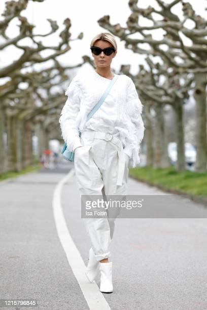 Influencer Gitta Banko, wearing a white fringed sweater and paperbag pants by Iro, white booties by Celine, topaz padded casette bag by Bottega...