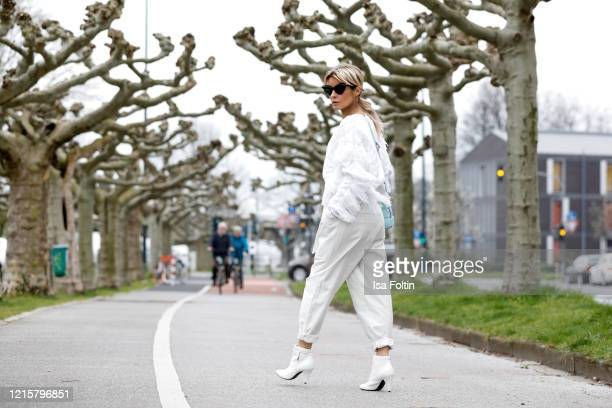 Influencer Gitta Banko wearing a white fringed sweater and paperbag pants by Iro white booties by Celine topaz padded casette bag by Bottega Veneta...