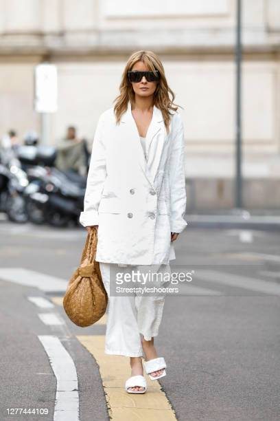 Influencer Gitta Banko, wearing a white oversize blazer and white pants by Annette Goertz, a white bralette by H&M, white padded BV lido sandals by...