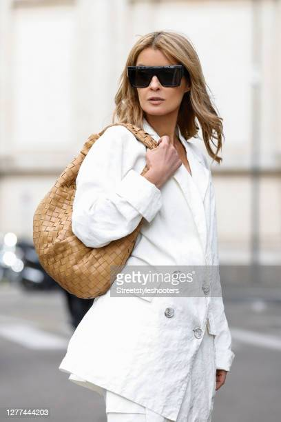Influencer Gitta Banko, wearing a white oversize blazer and white pants by Annette Goertz, a white bralette by H&M, a camel colored jodie bag by...