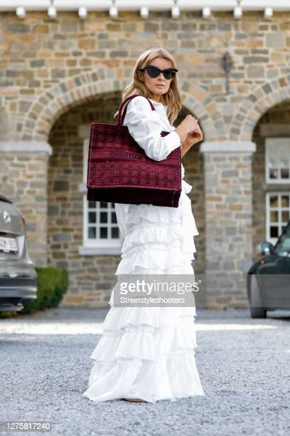 Influencer Gitta Banko, wearing a white oversize blouse and a white flouncy skirt by Helene Galvas, white flats by Chanel, a book tote bag burgundy...