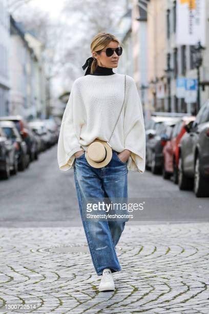 Influencer Gitta Banko wearing a white oversize pullover by SoSUE, light blue grandpa denim jeans by Saint Lauent, white sneaker by Y-3 , a black...