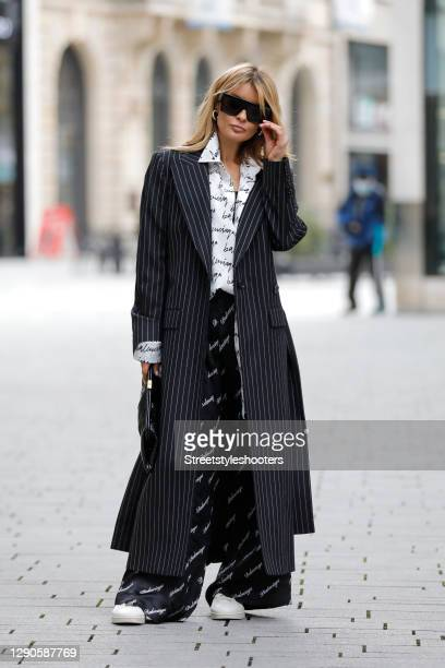 Influencer Gitta Banko wearing a white oversize silk blouse with black all over logo print by Balenciaga, black silk pants with white all over logo...