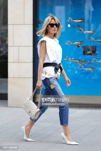 Influencer Gitta Banko wearing a white top with shoulder pads by The Frankie Shop, a Jeans by Vivienne Westwood, white pumps by Balenciaga, a golden...