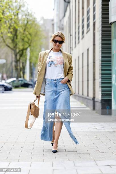 Influencer Gitta Banko wearing a white t-shirt with front print by Re/Done, a slouchy denim jeans maxi skirt with high slits by Dondup, a beige...