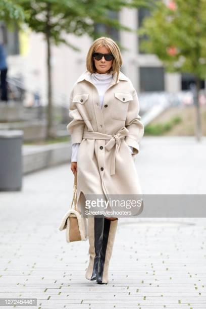 Influencer Gitta Banko wearing a white turtle neck pullover by Brunello Cucinelli, a beige blouse dress with a belt by Brunello Cucinelli, black and...