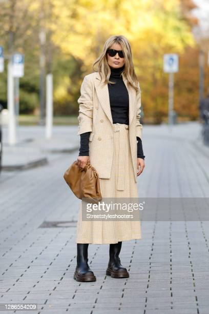 Influencer Gitta Banko wearing a yellow and white blazer with houndstooth pattern and a matching midi length pleated skirt by Beatrice B, a black...