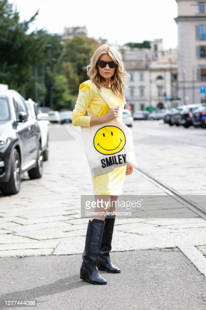 Influencer Gitta Banko, wearing a yellow colored tie-dye dress by Maare, black knee high boots by Isabel Marant, a tote bag with a smiley by Stuff...