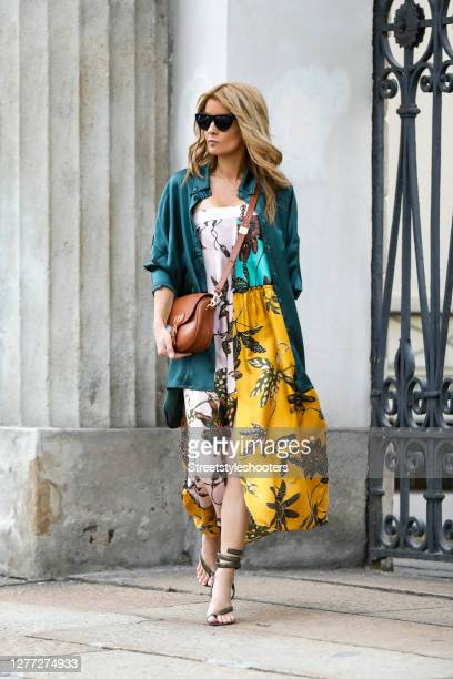 Influencer Gitta Banko, wearing a yellow flower printed bandeau dress by Dorothee Schumacher, a cognac colored bobby bag by Dior, a green oversized...